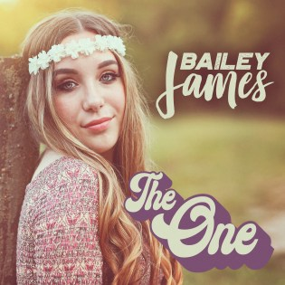 "The cover art for Bailey's single ""The One"" Bailey James is posing next to a post with grass and trees in the backround."