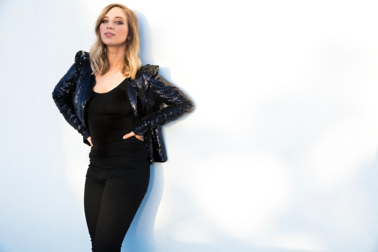 Olivia Lane is wearing all black with a leather jacket. She is standing in front of grey/white background.