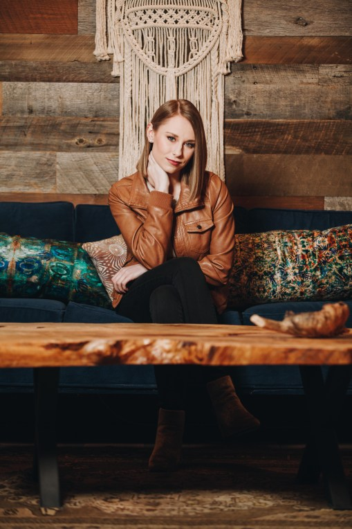 Alyssa Trahan sitting on a sofa in a brown leather jacket in front of a wooden wall.