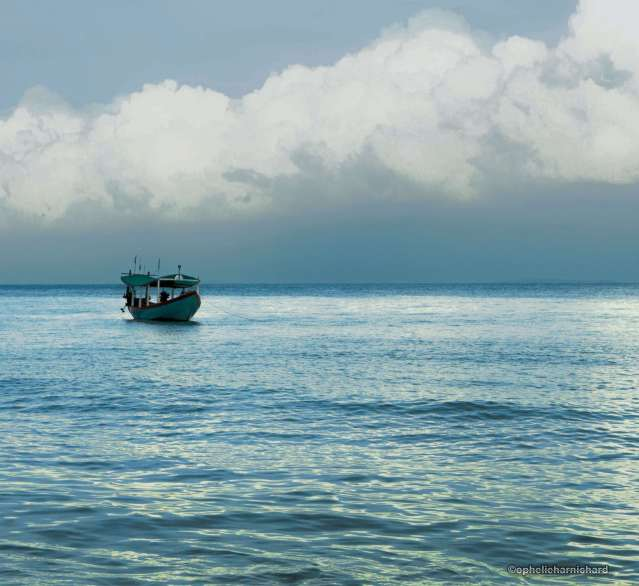 Travel-photography-gallery-Photography of a boat on the sea and clouds reflected in koh rong cambodia