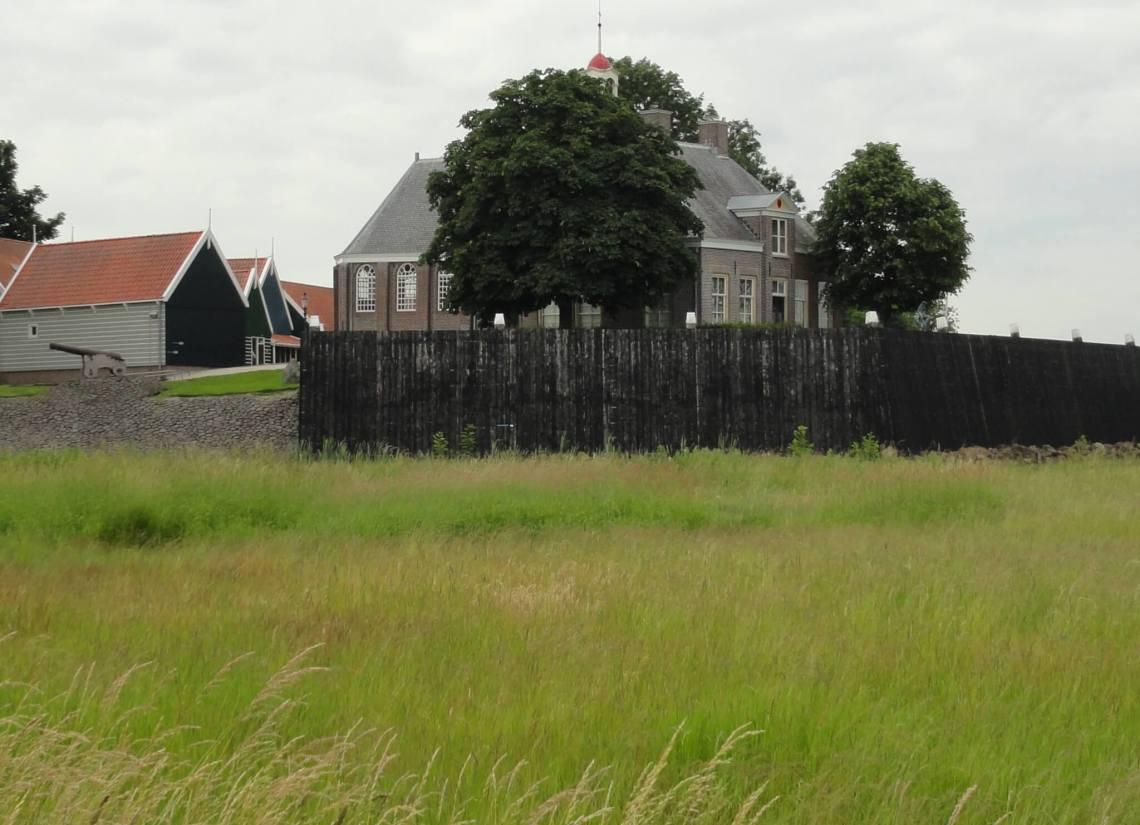 waterkering en kerk van Schokland op een hoger gelegen gedeelte tussen het gras