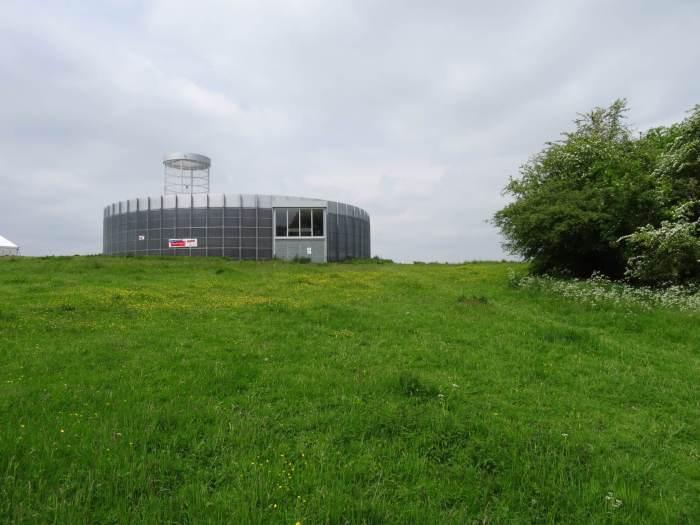 Rond vormgegeven bezoekerscentrum op een groene heuvel