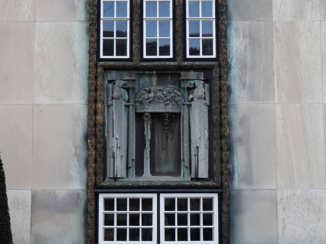 Verguld koper rondom raamkozijn en beeldhouwwerk tussen de verdiepingen
