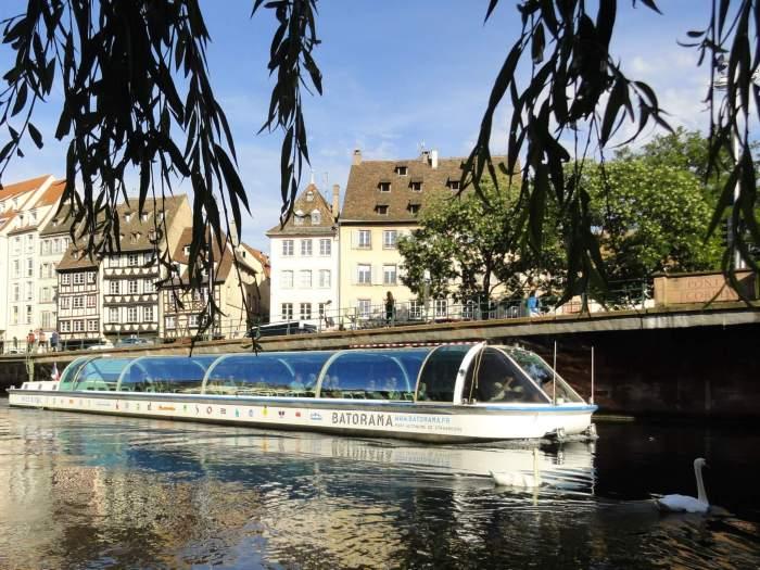 Rondvaartboot in binnenwater met vakwerkhuizen op de achtergrond