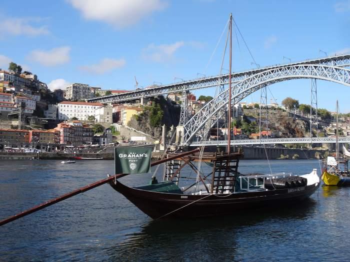 Een oud vrachtschip (Barcos Rabelo) ligt aan de kade in Porto met vaten Graham's port
