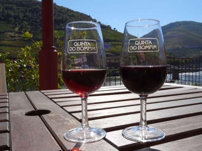 2 glaasjes rode port te midden van heuvellandschap Alto Douro