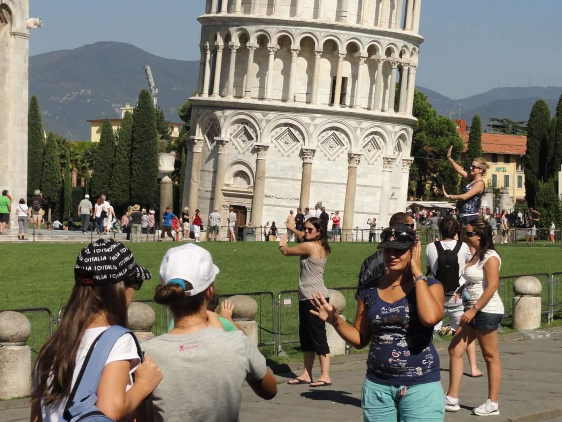 Toeristen doen alsof ze de scheve toren van Pisa omduwen