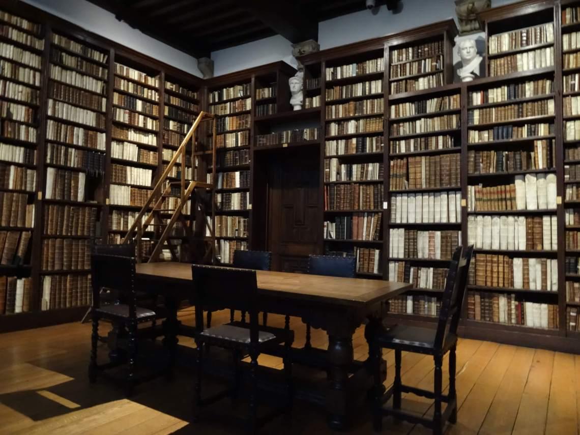 Antieke boekenkasten bedekken de muren in museum Plantin Moretus