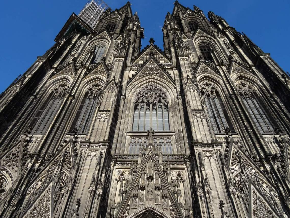 Twee gotische torenspitsen van kathedraal van Keulen steken de blauwe lucht in