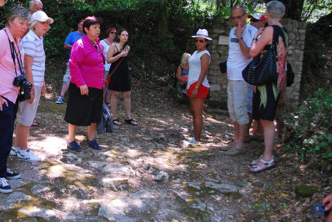 Groep toeristen rondom gids met felroze blouse