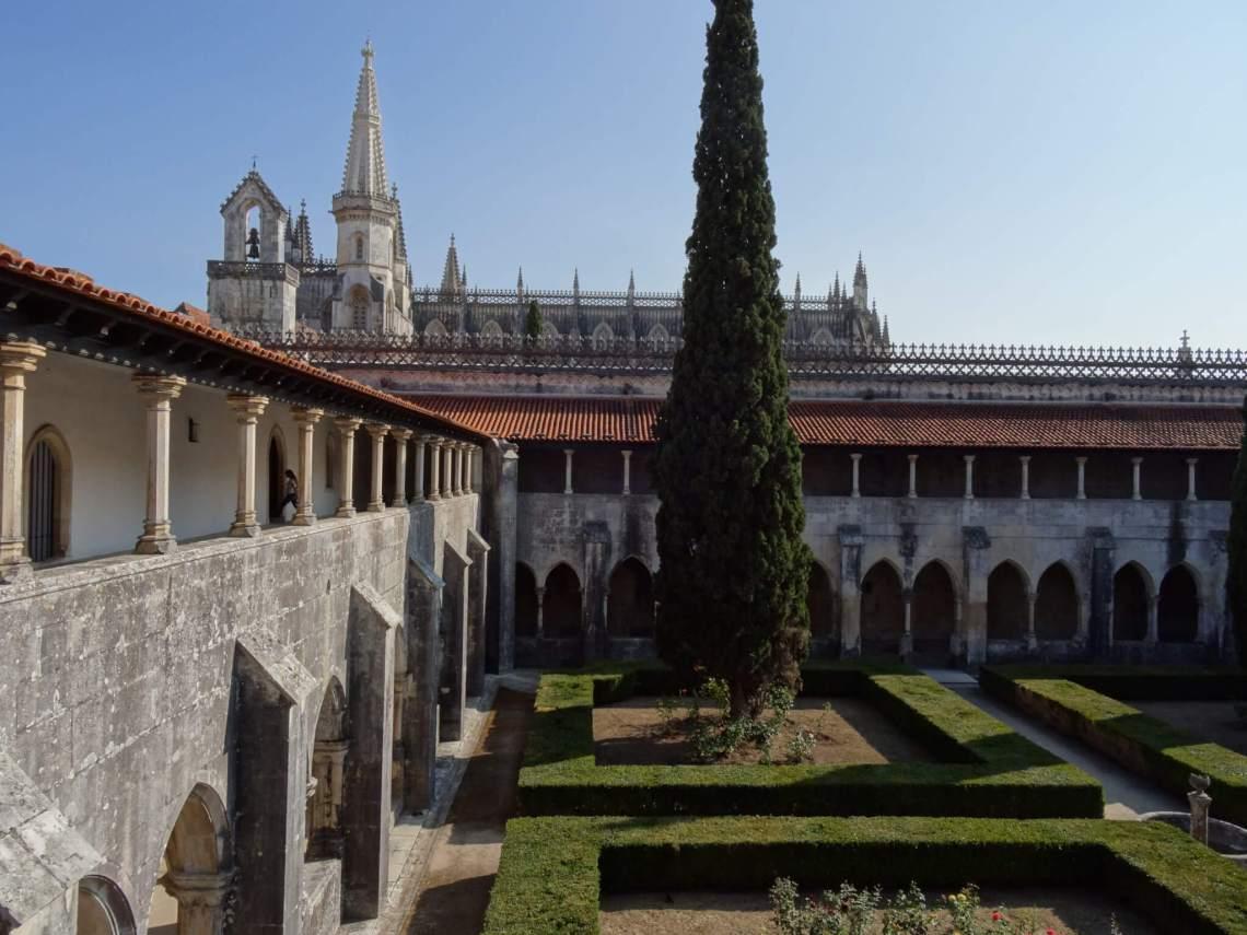 Binnentuin klooster Batalha met strakke hagen en hoge conifeer