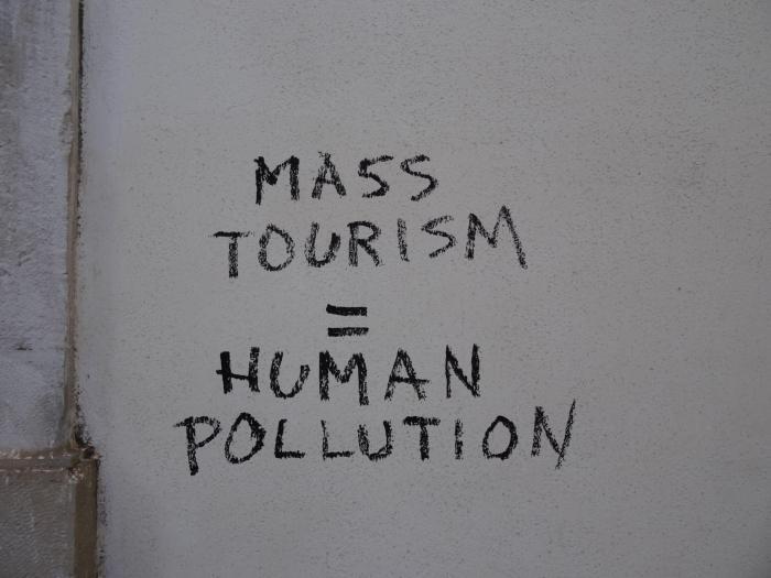 "massatoerisme = menselijke vervuiling"" graffityleus op muur in Lissabon"