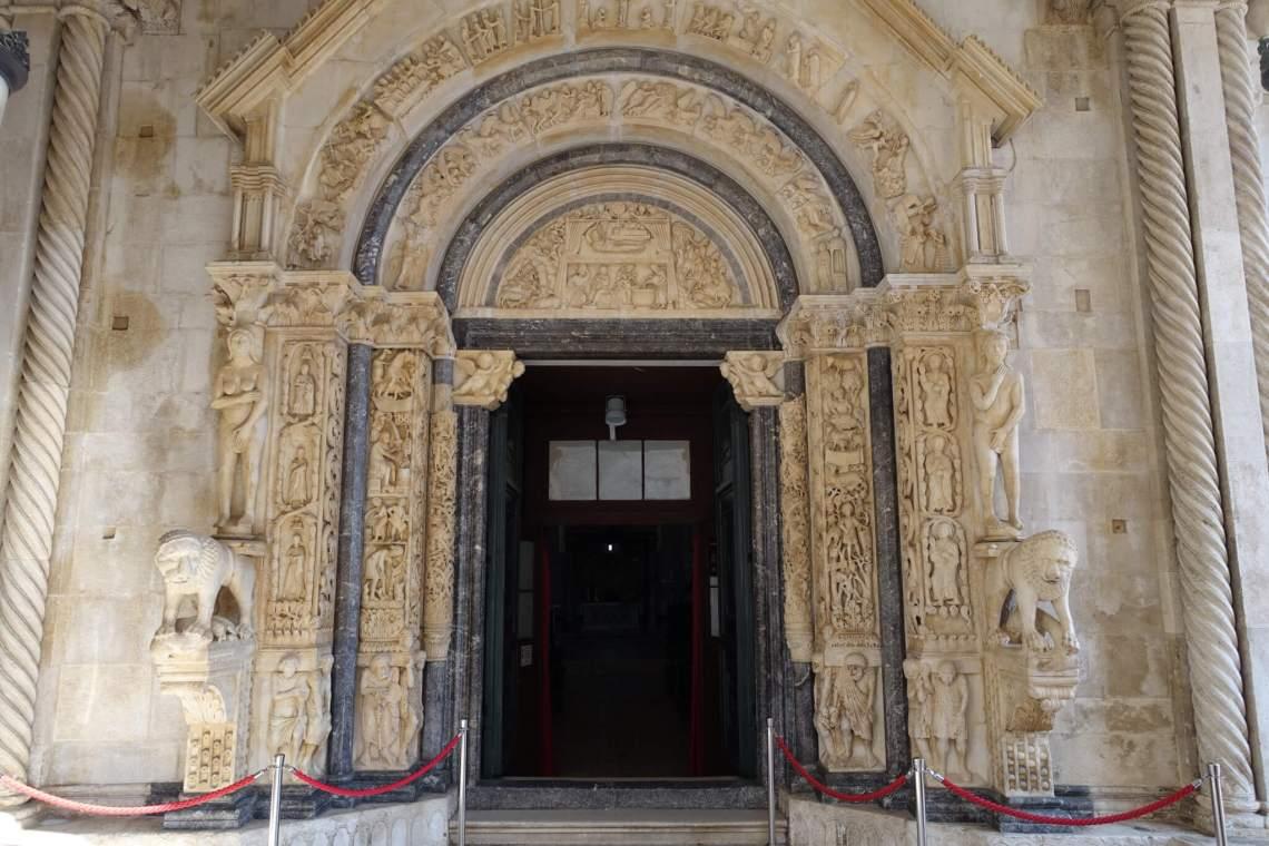 Zandkleurige zuilen en granieten bogen met beeldfiguren rondom ingang kathedraal