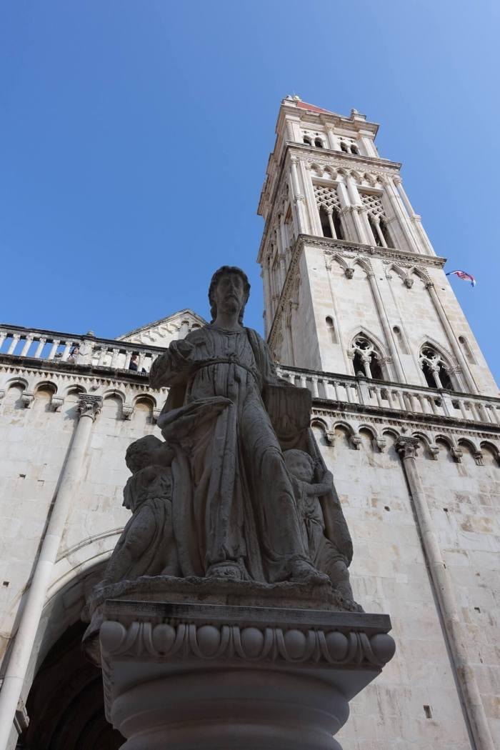 standbeeld van de Heilig Laurentius met op de achtergrond de klokkentoren van de kathedraal van Trogir