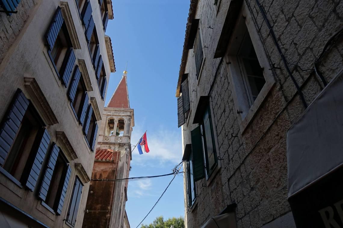 Straatbeeld met klokkentoren in Trogit