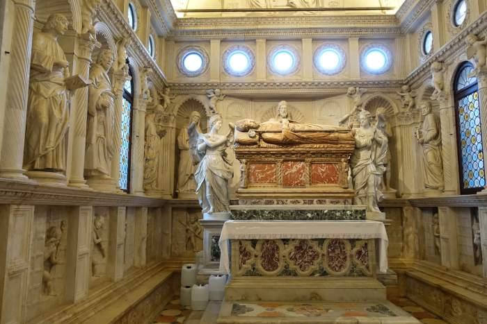 Sarcofaag van liggend figuur omringd door heiligenbeelden