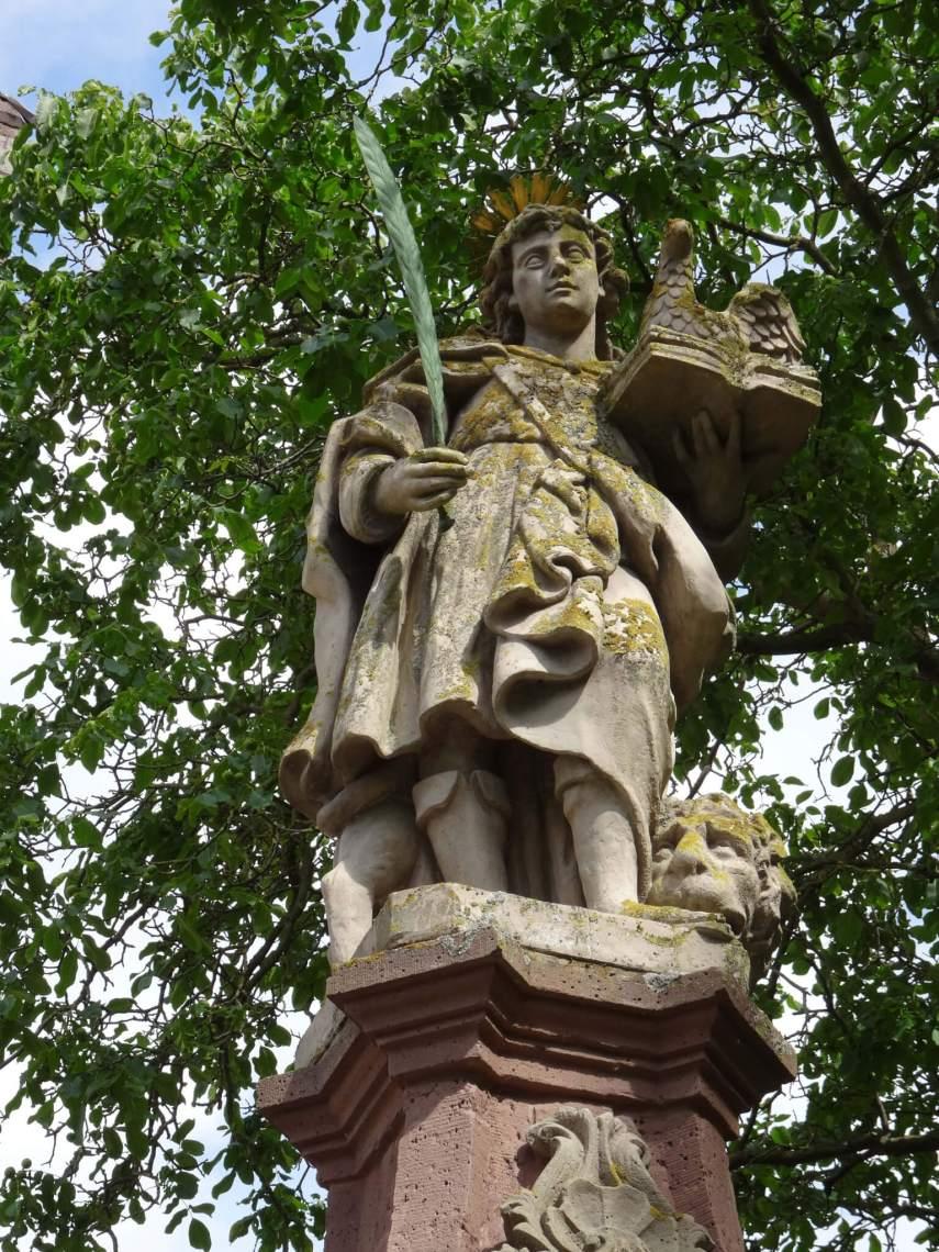 Standbeeld van Sint Vitus voor het klooster van Corvey met aan zijn voeten een leeuw, en een adelaar bij zijn hoofd