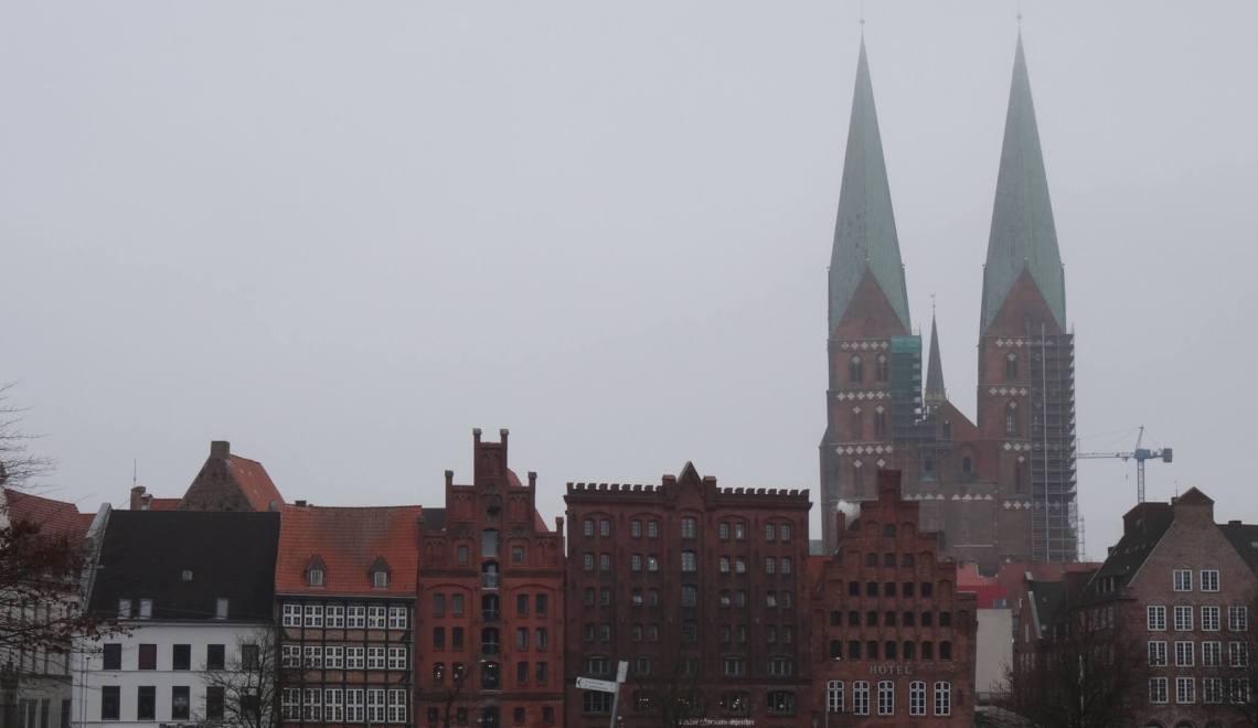 Stadsgezicht Lübeck met koophuizen en 2 spitse kerktorens