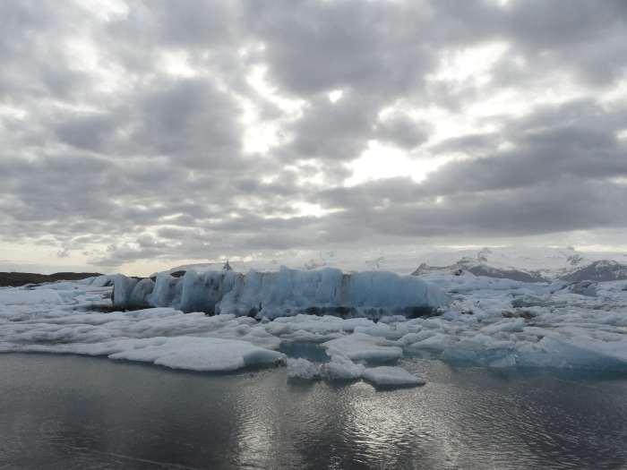 IJsschotsen drijven op ijsmeer in IJsland onder grijze wolkenlucht