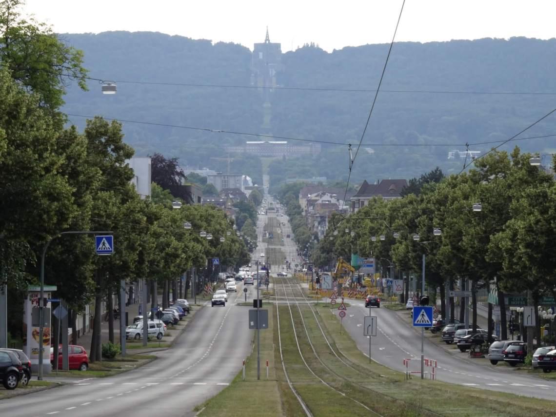 Lange laan met tramrails die leidt naar berg met kasteel en bergslot