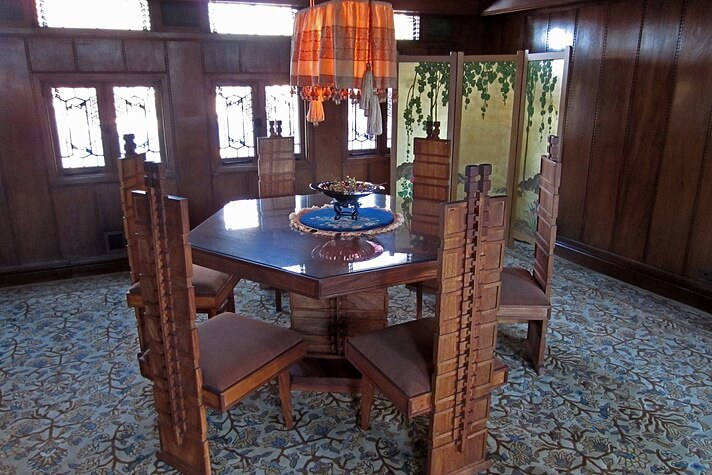 Zeshoekige eettafel met stoelen die in een stokroospatroon in de rug dragen