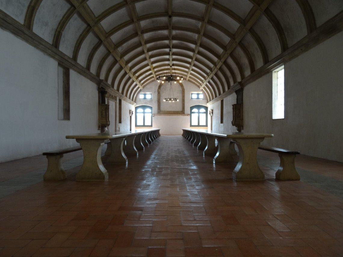Lange halvornmge zaal met stenen banken en tafel