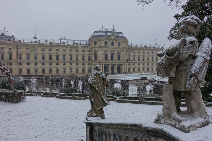 Besneeuwde, stenen standbeelden op ene trapleuning kijken naar de lange achtergevel van residentie Würzburg