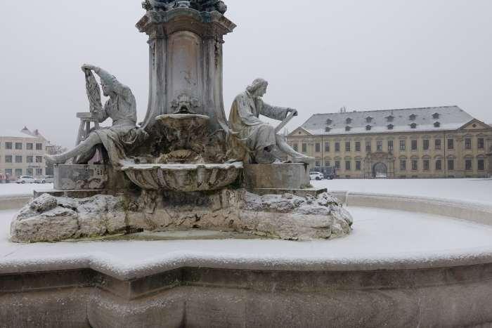 Sculpturen van een beeldhouwer en een dichter op een sokkel in winters stadsgezicht