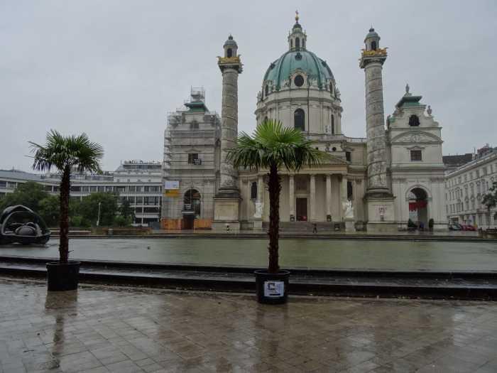 Karlskirche met koepeldak, twee zuilen en twee palmbomen