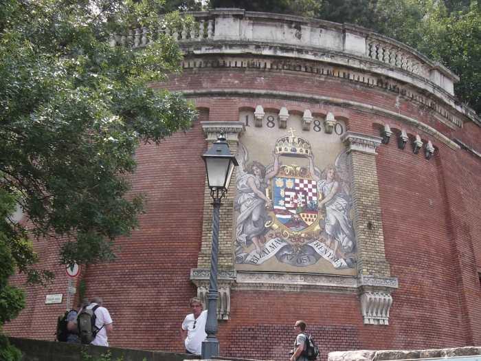 Rood bakstenen stadsmuur met tekening van wapenschild en Stefanskroon gedragen door twee engelen