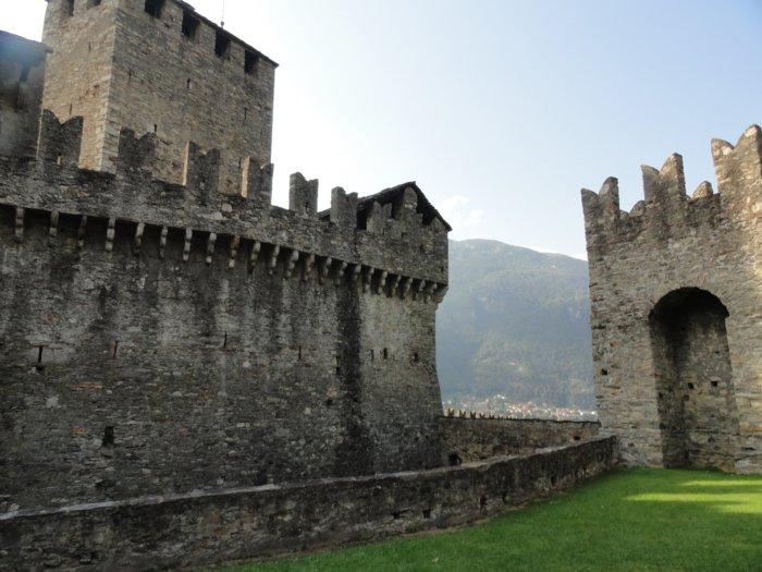 Granietgrijze kasteelmuren met zwaluwstaartkantelen en uitkijktoren