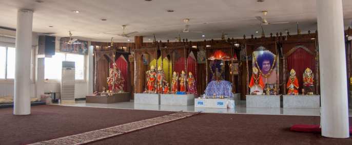 The temple features a large room filled with various religious icons, with a rug dividing areas for men and women to stand. (Alec Cowan/Crossings)