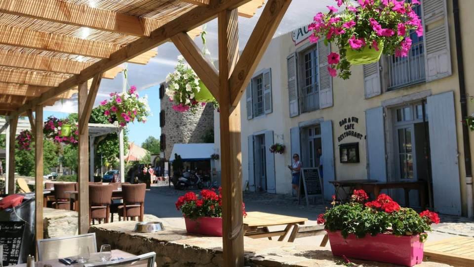 Les restaurants du village de Lavoûte-Chilhac ont des terrasses en bois avec des géraniums fleuris