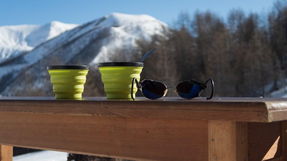 Bols de petit déjeuner sur un banc en bois avec lunettes de montagne
