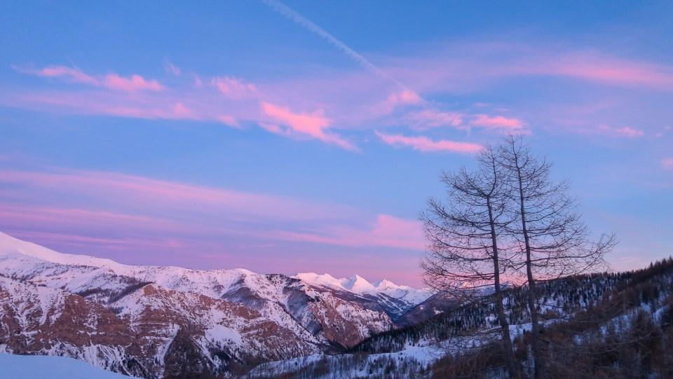 Paysage de montagne, ciel rose et bleu avec mélèzes au coucher du soleil