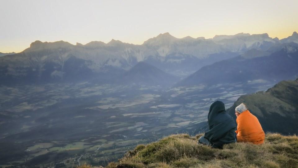 Jeunes filles avec couvertures qui assistent au lever de soleil sur le sommet du Mont Aiguille