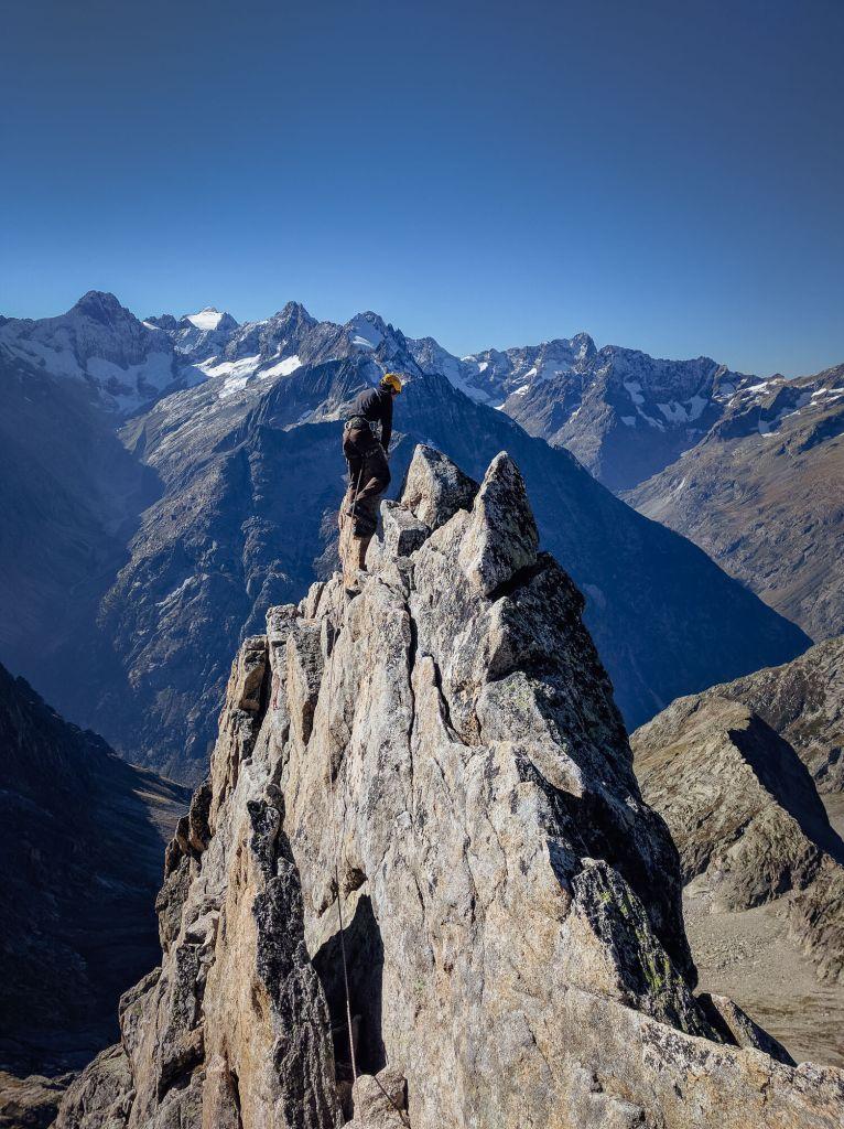 Une personne arrive au sommet de l'Aiguille Dibona sur fond de ciel bleu