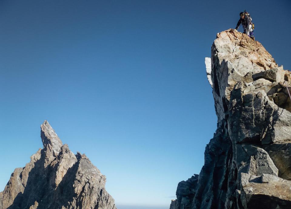 Homme au sommet d'un pic rocheux sur la Meije
