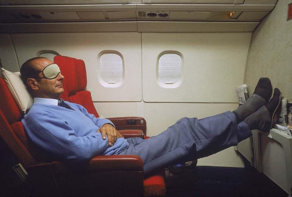 Jacques Chirac en pantoufles et masque sur les yeux, se reposant lors d'une sieste à bord du Concorde l'emmenant en Nouvelle-Calédonie.