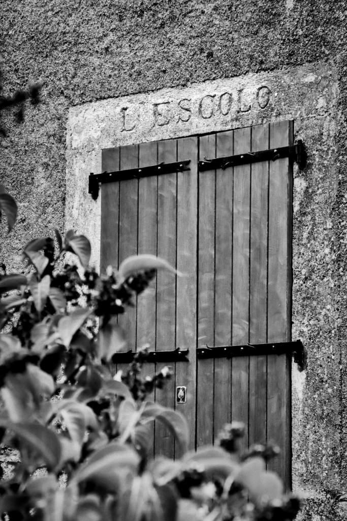 """Cliché en noir et blanc de la porte de l'école de Cantobre, """"Escolo"""" en langue d'Oc"""