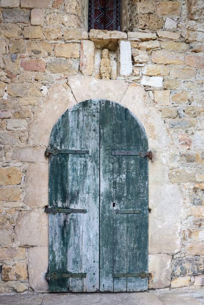 La porte bleue en bois patiné de l'Eglise de Saint-Etienne-de-Cantobre