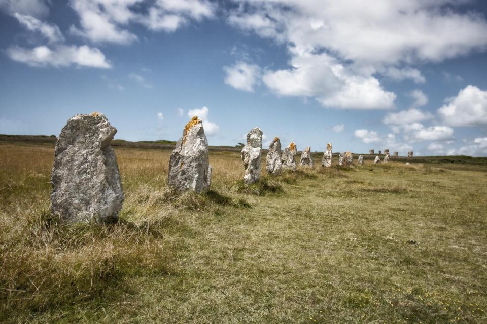 Alignements de menhirs dits de Lagatjar à Camaret-sur-Mer, dans un champ sous un ciel de nuages blancs