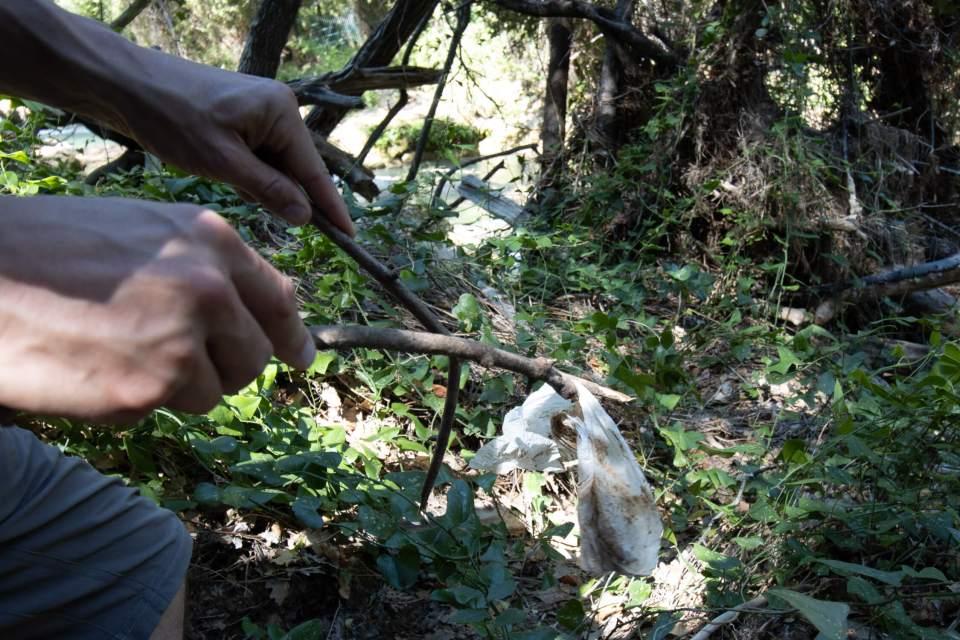Deux mains sont en train de saisir une lingette souillée avec des bâtons de bois, à Sillans-la-Cascade