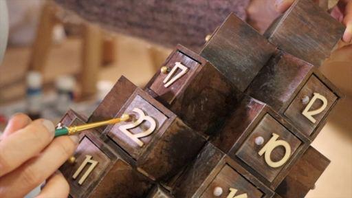 Application de peinture dorée sur les boutons de portes du calendrier de l'avent