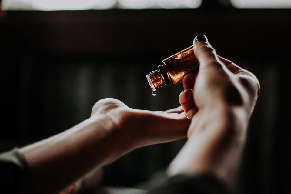On voit les mains d'une femme qui verse dans sa paume une goutte d'huile essentielle