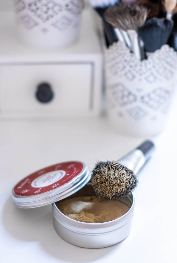 Shampoing sec maison dans un boite en fer blanc avec pinceau à maquillage pour l'application.