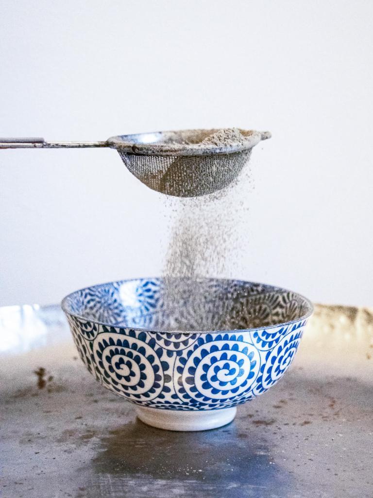Shampoing sec maison en poudre qui passe au travers d'un tamis sur un bol