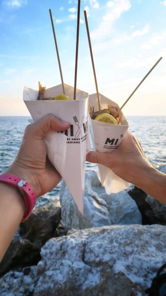 Cornets de fruits de mer à emporter dégustés en apéro au coucher du soleil sur la digue de Riomaggiore (Cinque Terre)
