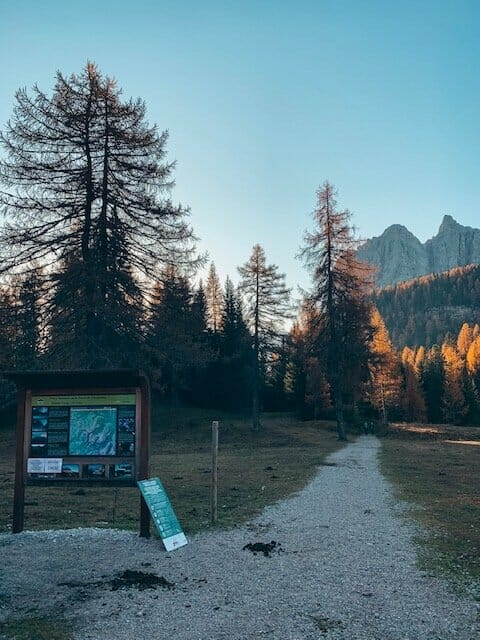a wood board with the trailhead to the lago di sorapis hiike and mountains in the background. There is early morning light on the trees, casting an orange glow.
