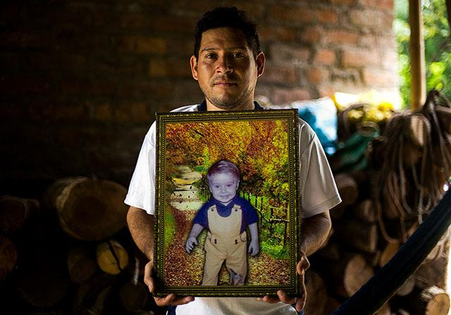 Douglas Romero holds the photo that his father used to locate him, after finding the image in the office of a sub-lieutenant and recognizing his son, who had been stolen following a military operation. Photo: Fred Ramos